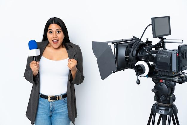 Reporter femme colombienne tenant un microphone et rapportant des nouvelles sur le mur blanc célébrant une victoire en position de vainqueur