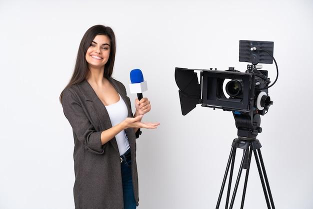 Reporter femme tenant un microphone et rapport de nouvelles sur blanc isolé étendant les mains sur le côté pour inviter à venir