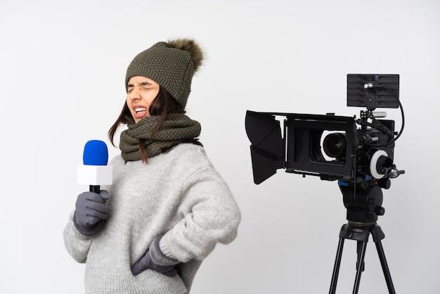 Reporter femme tenant un microphone et rapportant des nouvelles sur un mur blanc isolé souffrant de maux de dos pour avoir fait un effort