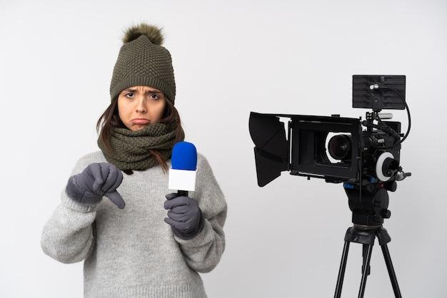 Reporter femme tenant un microphone et rapportant des nouvelles sur le mur blanc montrant le pouce vers le bas avec une expression négative