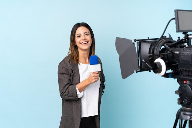 Reporter femme tenant un microphone et rapportant des nouvelles sur le mur bleu