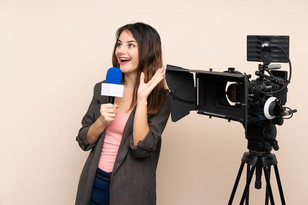 Reporter femme tenant un microphone et rapportant des nouvelles sur le mur avec une expression faciale surprise