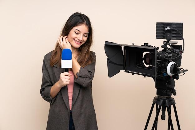 Reporter femme tenant un microphone et rapportant des nouvelles sur le mur isolé en riant