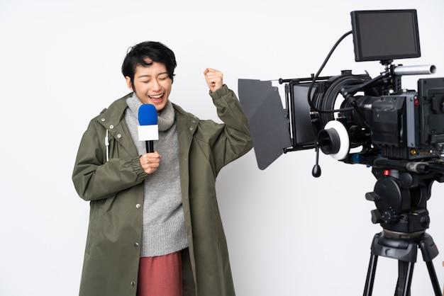 Reporter femme vietnamienne tenant un microphone et rapportant des nouvelles célébrant une victoire