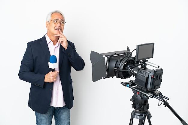 Reporter homme brésilien d'âge moyen tenant un microphone et rapportant des nouvelles isolées sur fond blanc ayant des doutes et pensant