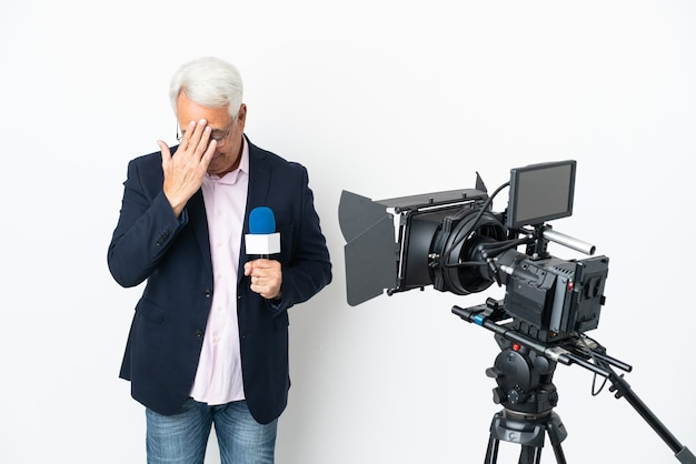 Reporter homme brésilien d'âge moyen tenant un microphone et rapportant des nouvelles isolées sur fond blanc avec une expression fatiguée et malade