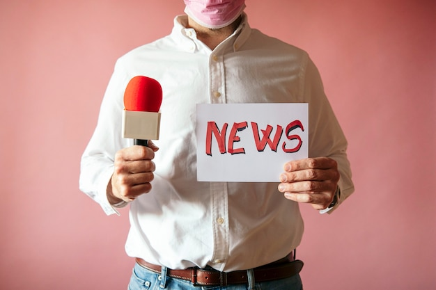 Reporter tenant une pancarte avec le mot news écrit et microphone en main avec fond rose