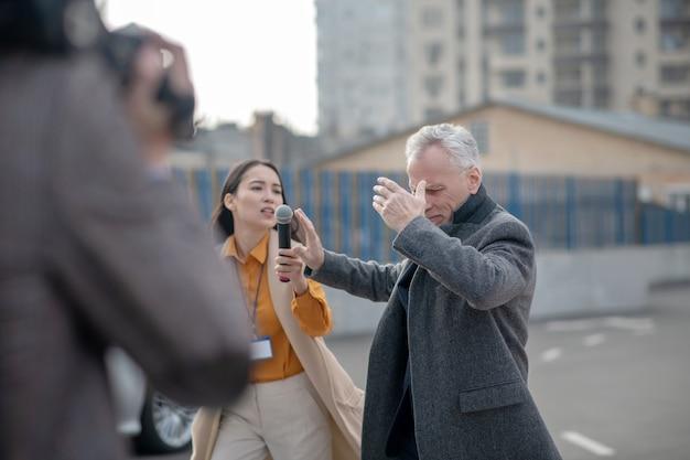 Reporters avec caméra vidéo rencontre un homme d'affaires célèbre à côté de son bureau