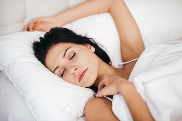 Repos après une dure journée. belle jeune femme dormant en position couchée dans le lit à la maison