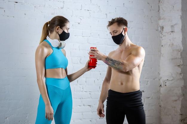 Repos. athlètes professionnels s'entraînant sur fond de mur de briques portant des masques faciaux. sport pendant la quarantaine de la pandémie mondiale de coronavirus. jeune couple pratiquant dans la salle de gym en utilisant l'équipement en toute sécurité.