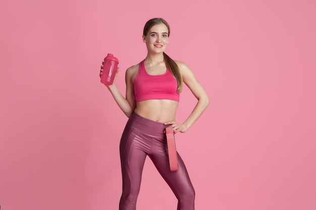 Repos. belle jeune athlète féminine pratiquant, portrait rose monochrome. modèle caucasien de coupe sportive avec gourde. musculation, mode de vie sain, concept de beauté et d'action.