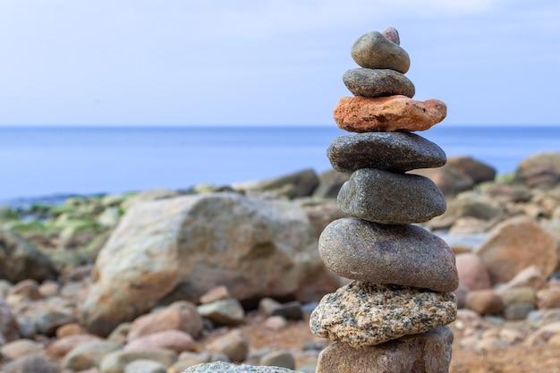 Repos et vacances à la mer. pyramide de pierres au bord de la mer à la journée ensoleillée. plage de galets, belle vue. concept de vie équilibrée, d'harmonie et de détente.