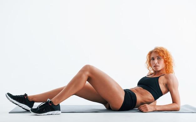 Repose sur le tapis roulant. bodybuilder femme rousse est en studio sur un espace blanc.