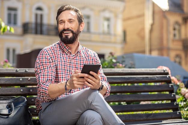 Reposez-vous. joyeux homme barbu souriant assis sur le banc tout en tenant un gadget moderne