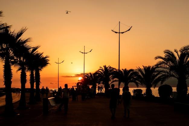 Reposez-vous sur la mer noire en géorgie dans la station balnéaire de batumi. coucher de soleil sur la promenade maritime.