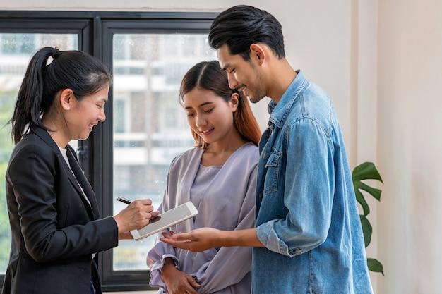 Le représentant de vente offre la liste de prix de l'immobilier et la condition d'achat ou de location du contact