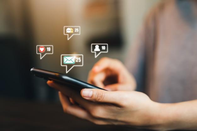 Réseau de communication concept. femme main presse téléphone et affiche l'icône d'email sur le mobile.