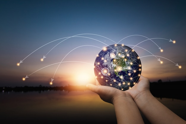 Réseau social mondial et connexion internet sur des données abstraites dans le monde entier concept cyberespace, gros plan main tenant la terre de réseautage sans fil se connecter avec les gens par la ligne de technologie 5g en ligne au coucher du soleil