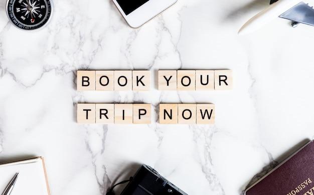 Réservez votre voyage maintenant le texte de scrabble sur la table de marbre avec des accessoires de voyage