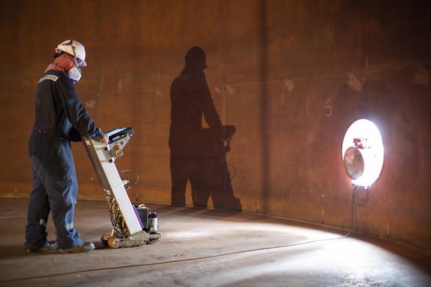 Le réservoir d'analyse du plancher d'inspection des travailleurs masculins du mur de rouille perd de l'épaisseur dans la plaque inférieure pour confiner