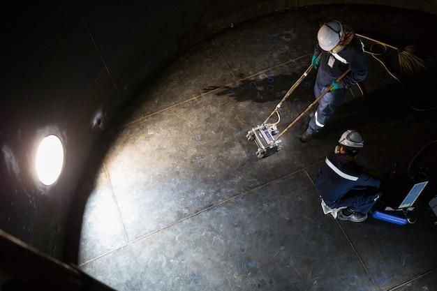 Réservoir d'analyse d'inspection de deux travailleurs masculins de la plaque inférieure d'épaisseur de rouille à confiné