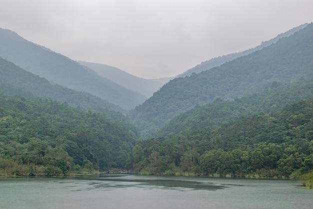Le réservoir après la pluie reflète les montagnes et les forêts