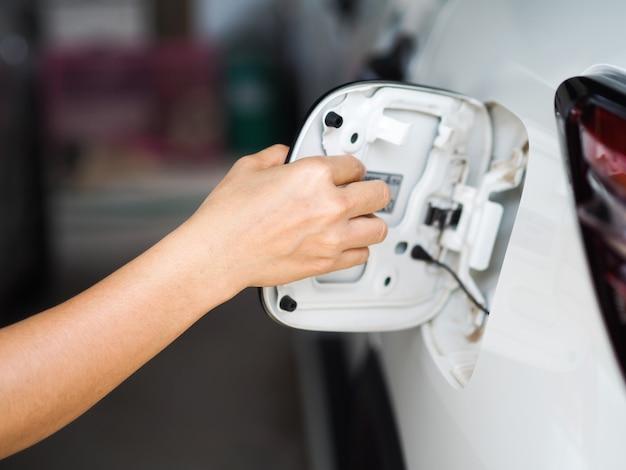 Réservoir de carburant de voiture ouvert à la main, main de mise au point sélective