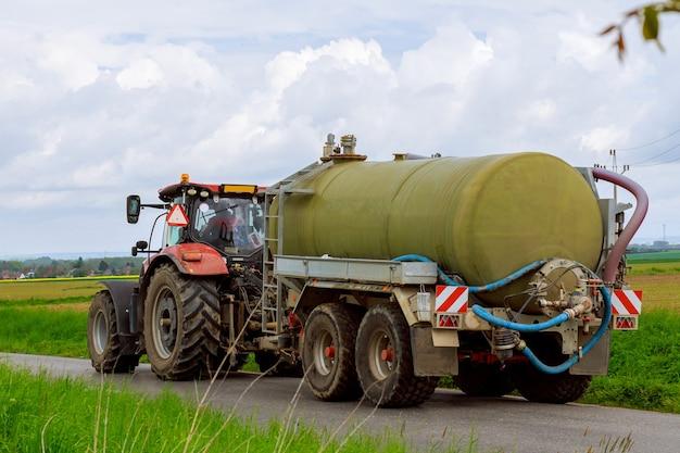 Réservoir d'eau pour semi-remorque. tracteur moderne avec une citerne, sur une route goudronnée près des champs agricoles.