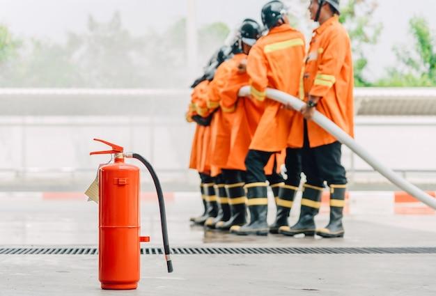 Réservoir rouge d'extincteur, au premier plan, pompier pulvérisant de l'eau à haute pression