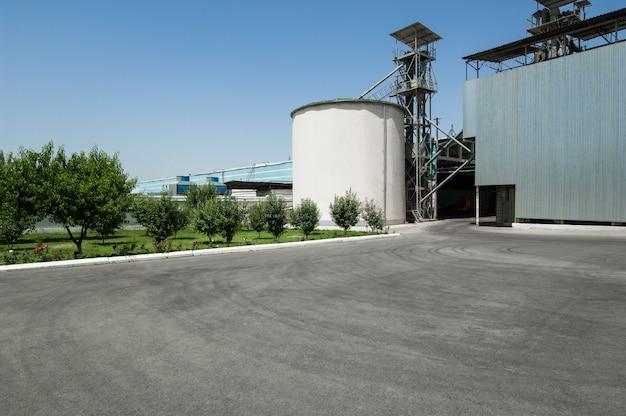 Réservoir de stockage et un bâtiment sur une ferme sous un ciel bleu. usine industrielle lourde