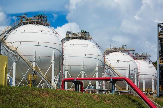Réservoirs de propane sphériques blancs contenant du gaz combustible fond bleu ciel.