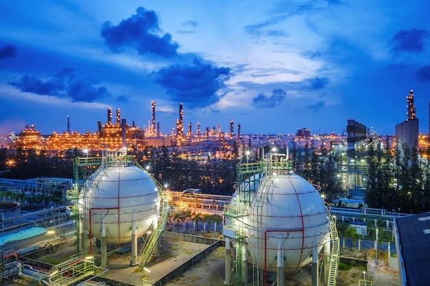 Réservoirs de sphère de stockage de gaz et pipeline dans une usine industrielle de raffinerie de pétrole et de gaz avec un domaine de l'industrie de l'éclairage scintillant au crépuscule