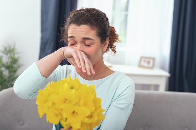 Résister à un parfum. jeune femme malade souffrant d'hypersensibilité tenant son nez en essayant de ne pas sentir l'odeur des jonquilles jaunes en fleurs