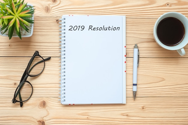 Résolutions 2019 avec carnet de notes, tasse à café noire, stylo et lunettes