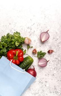 Respectueux de la nature. emballage de papier bleu artisanat avec des légumes