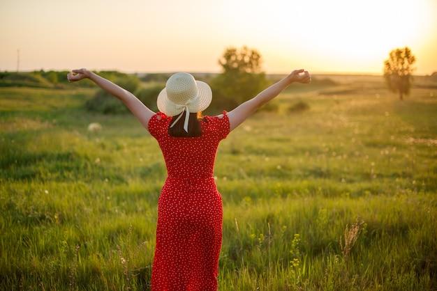 Respiration, femme aux mains levées profitant du soleil sur le terrain