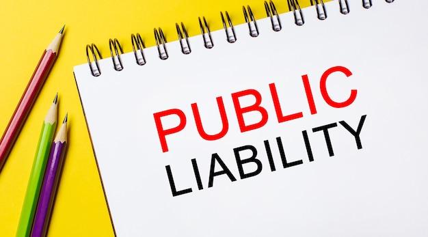Responsabilité publique texte sur un bloc-notes blanc avec des crayons sur un espace jaune