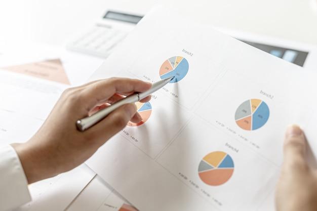 La responsable commerciale pointe vers le récapitulatif des ventes, elle vérifie les ventes de chaque agence, elle vérifie les informations avant de les présenter en réunion à la direction. concept de gestion des ventes.
