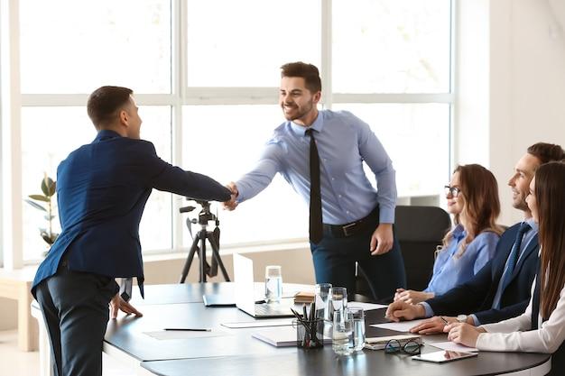Responsable des ressources humaines serrant la main du candidat après un entretien réussi