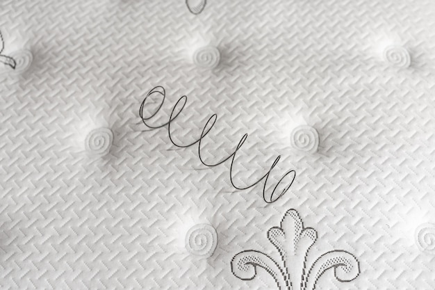 Ressort métallique sur un matelas blanc