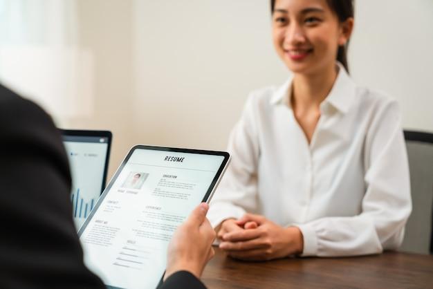 Les ressources humaines de l'entreprise (rh) tiennent en main une application de cv sur tablette.