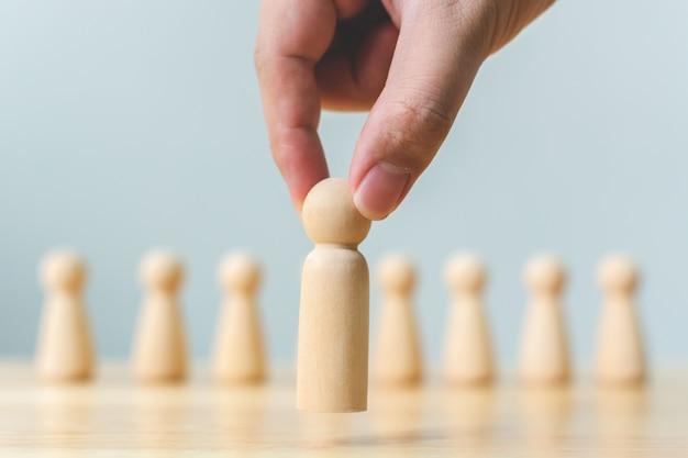 Ressources humaines, gestion des talents, recrutement, concept de chef d'équipe commerciale réussie. la main choisit un peuple en bois se démarquant de la foule.
