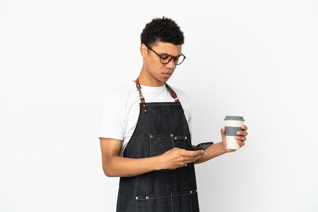 Restaurant garçon afro-américain isolé sur fond blanc tenant du café à emporter et un mobile