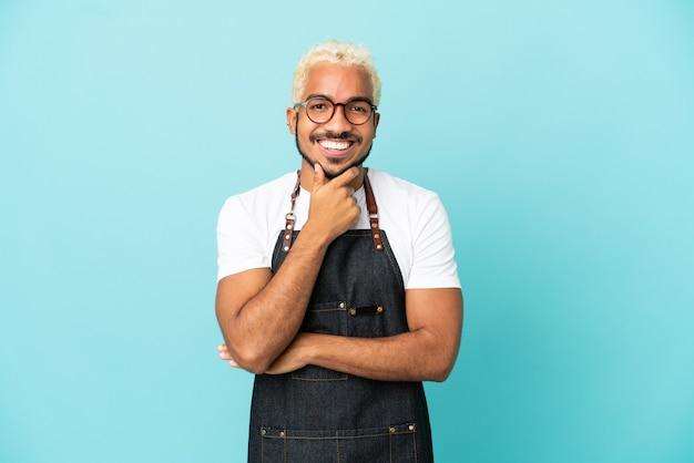 Restaurant garçon colombien homme isolé sur fond bleu avec des lunettes et souriant