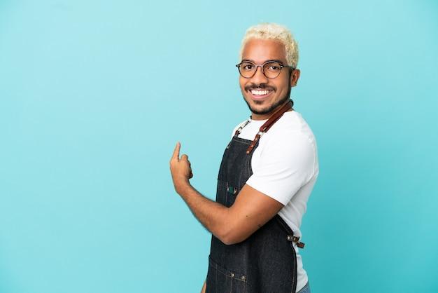 Restaurant garçon colombien homme isolé sur fond bleu pointant vers l'arrière