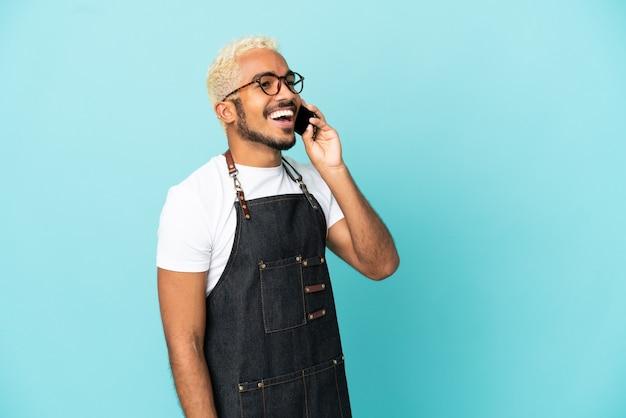 Restaurant garçon colombien isolé sur fond bleu en gardant une conversation avec le téléphone mobile