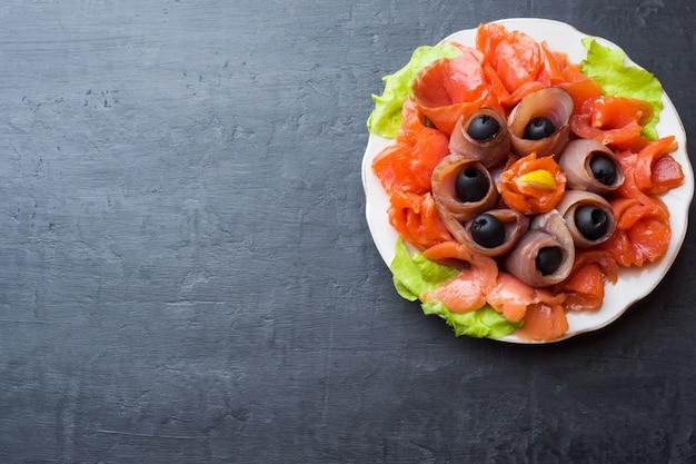 Restaurant gastronomique servant une assiette de sel fumé, de filets de poisson blanc cru et de saumon.