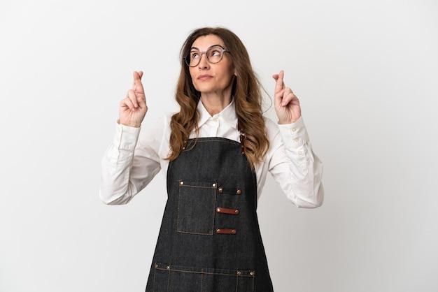 Restaurant serveur d'âge moyen femme isolée sur fond blanc avec croisement de doigts