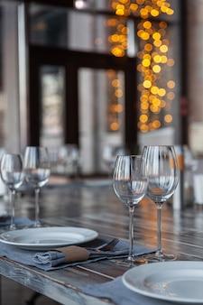 Restaurant véranda moderne servant, verres à vin et à eau, assiettes, fourchettes et couteaux, serviettes en textile, bokeh