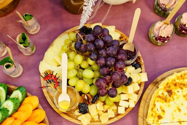 Restauration. assiette en bois avec raisins, fromage, confiture et miel dans de petits pots en verre.
